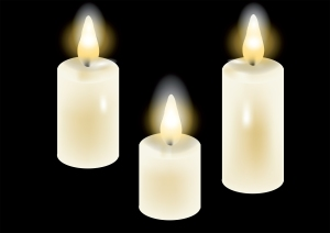 white candles. three candles isolated on a black background